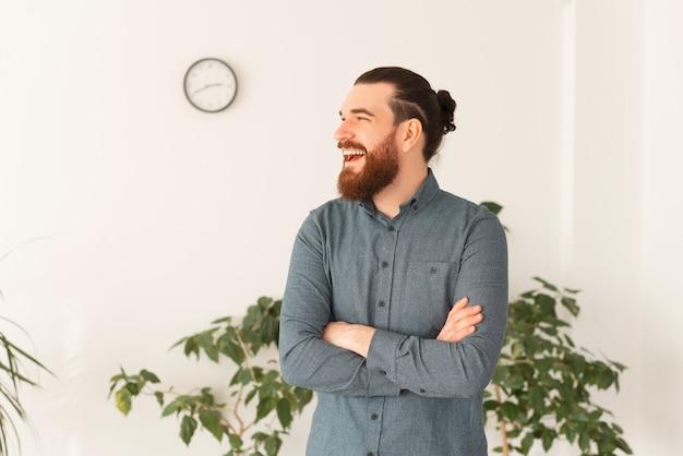 Portret przystojny urzędnik stojący ze skrzyżowanymi rękami i śmiejąc się