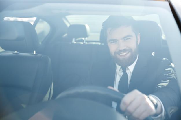 Portret przystojny uśmiechnięty biznesowy mężczyzna jedzie jego samochód