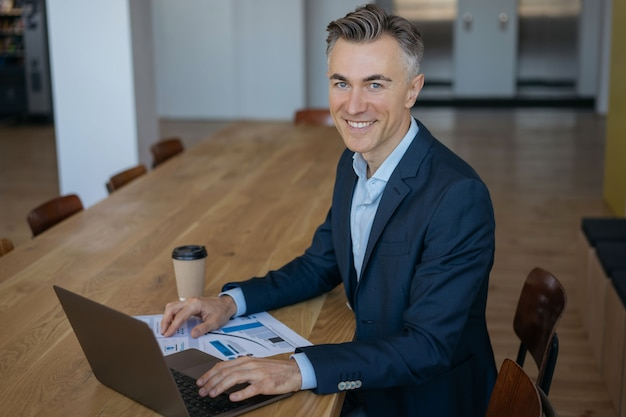 Portret przystojny uśmiechnięty menedżer siedzi w miejscu pracy, patrząc bezpośrednio