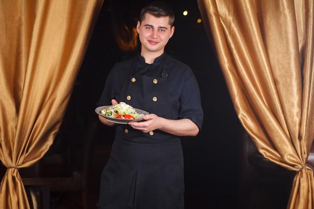 Portret przystojny uśmiechnięty męski szefa kuchni kucharz w jednolitej pozyci z wyśmienicie naczyniem przy kuchnią.