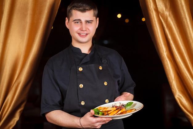 Portret przystojny uśmiechnięty męski szefa kuchni kucharz w jednolitej pozyci