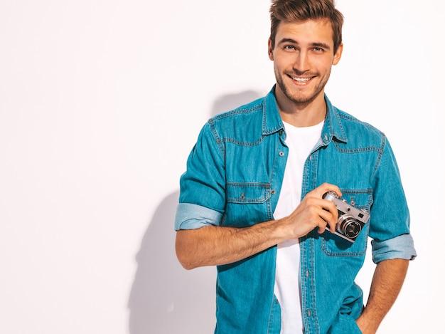 Portret przystojny uśmiechnięty mężczyzna jest ubranym lato cajgi odziewa. wzorcowa męska mienie rocznika fotografii kamera.