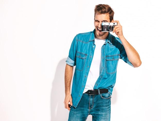 Portret przystojny uśmiechnięty mężczyzna jest ubranym lato cajgi odziewa. wzorcowa samiec bierze obrazek na starym rocznik fotografii kamerze.