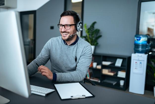 Portret przystojny uśmiechnięty mężczyzna z słuchawki pracuje na komputerze.