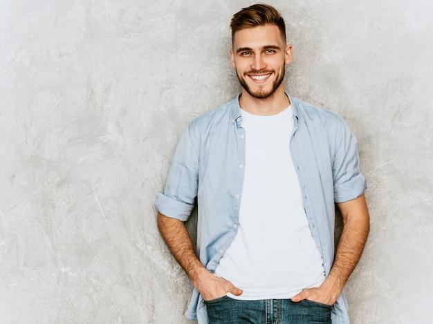 Portret przystojny uśmiechnięty młodego człowieka model jest ubranym przypadkową koszula odziewa. moda stylowy mężczyzna pozowanie