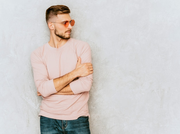 Portret przystojny uśmiechnięty młodego człowieka model jest ubranym przypadkowe lato menchie odziewa. moda stylowy mężczyzna pozowanie w okrągłe okulary przeciwsłoneczne