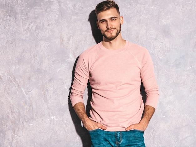 Portret przystojny uśmiechnięty młodego człowieka model jest ubranym przypadkowe lato menchie odziewa. moda stylowy mężczyzna pozowanie