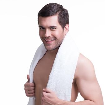 Portret przystojny uśmiechnięty młody człowiek z ręcznikiem - na białym tle.