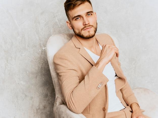 Portret przystojny uśmiechnięty modnisia biznesmena model jest ubranym przypadkowego beżowego kostium. siedząc w fotelu we wnętrzu