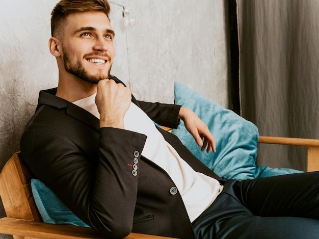 Portret przystojny uśmiechnięty modnisia biznesmena model jest ubranym przypadkowego czarnego kostium.