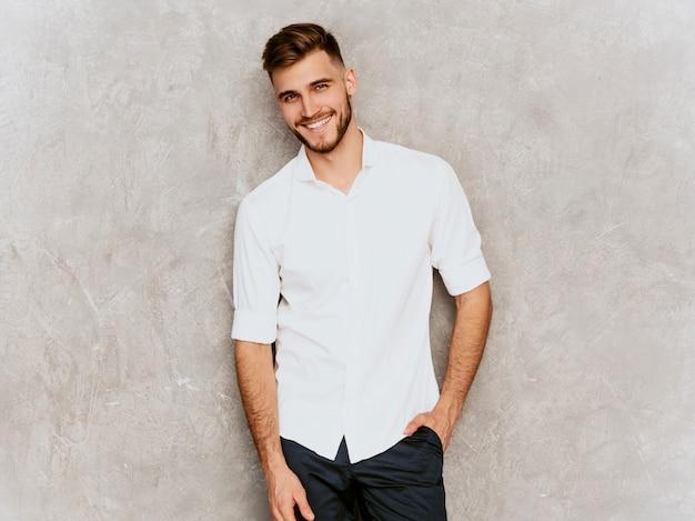 Portret przystojny uśmiechnięty modnisia biznesmena model jest ubranym przypadkowego lato białą koszula.