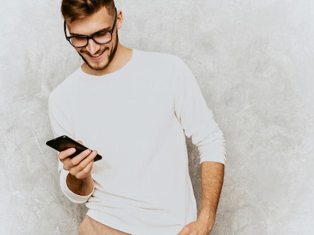 Portret przystojny uśmiechnięty modnisia biznesmena model jest ubranym przypadkowego lato bielu ubrania z telefonem komórkowym