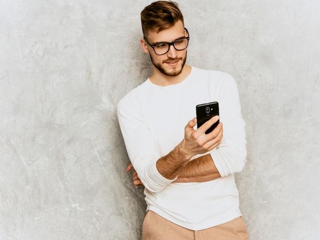 Portret przystojny uśmiechnięty modnisia biznesmena model jest ubranym przypadkowego lato bielu ubrania.
