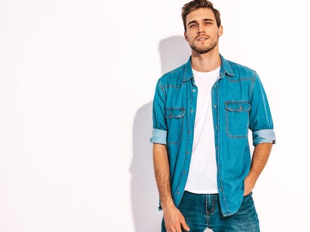 Portret przystojny uśmiechnięty stylowy młody człowiek model ubrany w dżinsy ubrania. moda mężczyzna