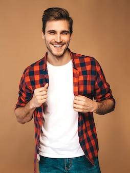Portret przystojny uśmiechnięty stylowy młody model mężczyzna ubrany w czerwoną kraciastą koszulę. moda mężczyzna pozowanie