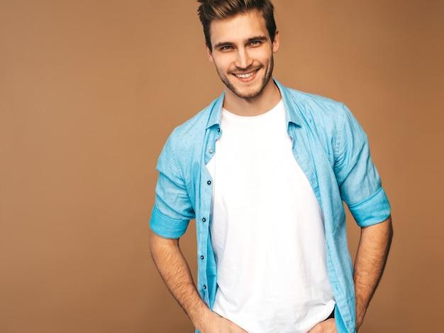Portret przystojny uśmiechnięty stylowy młody model mężczyzna ubrany w niebieską koszulę ubrania. moda mężczyzna pozowanie