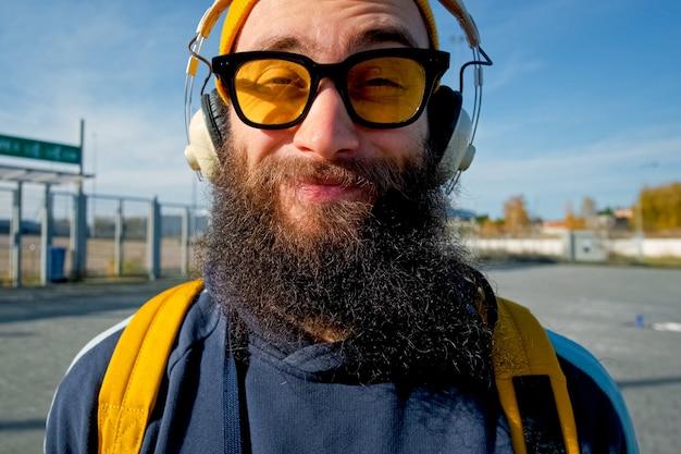 Portret przystojny w słuchawkach elektronicznych patrząc na kamerę