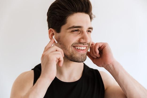 Portret przystojny wesoły uśmiechnięty szczęśliwy młody sportowiec odizolowywający nad białą ścianą słuchająca muzyka ze słuchawkami.