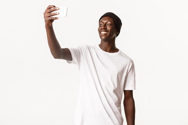 Portret przystojny wysoki facet afroamerykanin w czapce, biorąc selfie na smartfonie i uśmiechnięty szczęśliwy
