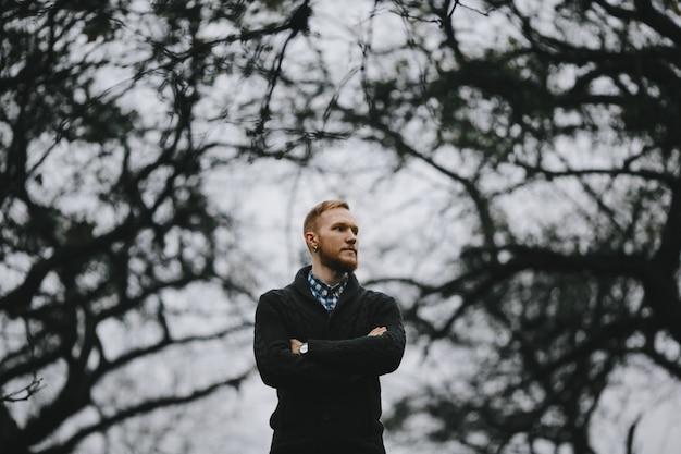 Portret przystojny wysoki mężczyzna stoi outside w gęstej jesieni