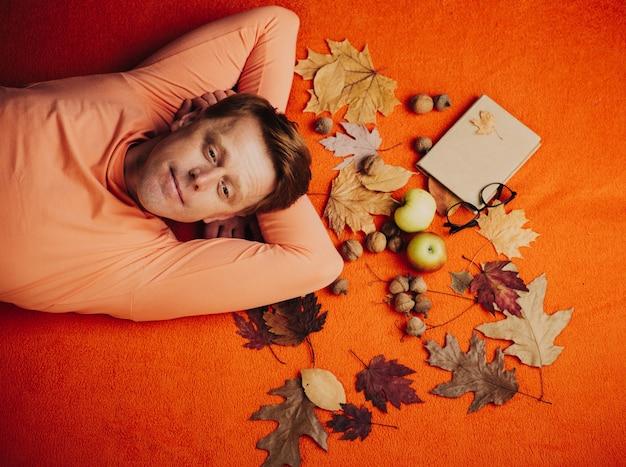 Portret przystojny zabawny mężczyzna z rudymi włosami. atrakcyjny młody człowiek w sezonowych ubraniach ze złotym liściem.