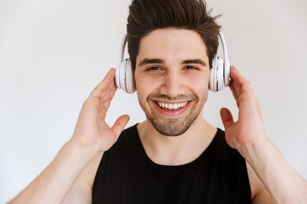 Portret przystojny zadowolony uśmiechnięty młody sportowiec odizolowywający nad białą ścianą słuchająca muzyka z hełmofonami.