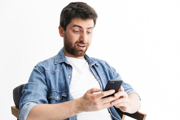 Portret przystojny zszokowany brodaty mężczyzna ubrany w zwykłe ubrania, siedzący na krześle na białym tle nad białą ścianą, trzymający telefon komórkowy