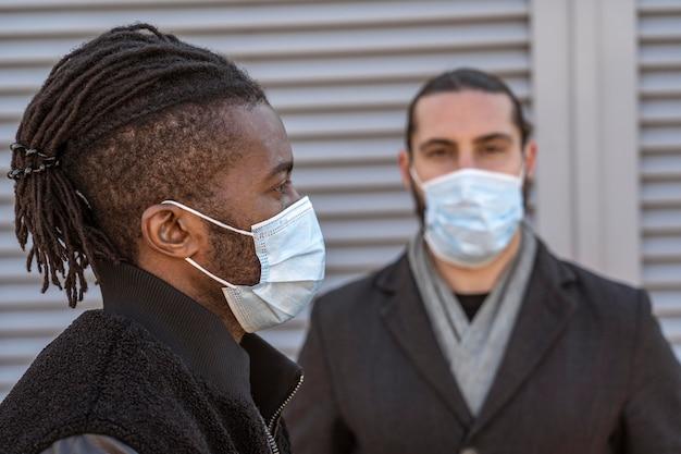 Portret przystojnych mężczyzn noszących maski medyczne