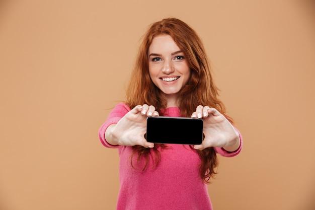 Portret radosna atrakcyjna rudzielec dziewczyna pokazuje smartphone