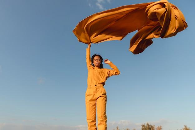 Portret radosna kobieta z żółtym płótnem w naturze