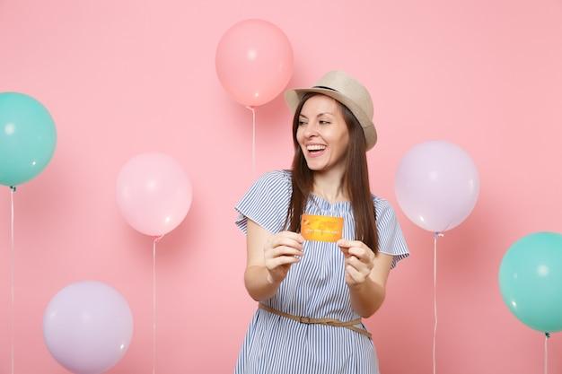 Portret radosna piękna młoda kobieta w słomkowym letnim kapeluszu niebieską sukienkę trzymającą kartę kredytową patrząc na bok na różowym tle z kolorowymi balonami. urodziny wakacje party ludzie szczere emocje.