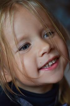 Portret radosna romantyczna mała dziewczynka z dużymi niebieskimi oczami i otwartym uśmiechem od europa wschodnia, zakończenie, ciemny tło