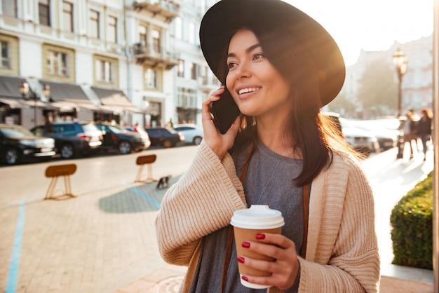 Portret radosna stylowa kobieta opowiada na telefonie komórkowym