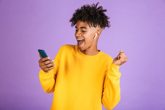 Portret radosnego afroamerykanina uśmiechającego się i trzymającego smartfona podczas słuchania muzyki przez słuchawkę bluetooth, na białym tle na fioletowym tle