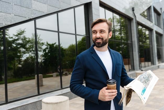 Portret radosnego biznesmena w kurtce pijącego kawę z papierowego kubka i czytającego gazetę stojąc na zewnątrz w pobliżu budynku