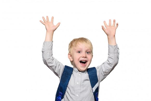 Portret radosnego blond ucznia z tornister. ręce do góry. izolować