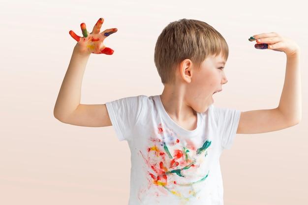 Portret radosnego małego chłopca z kolorowymi pomalowanymi dłońmi