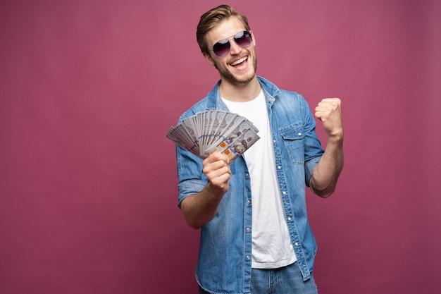 Portret radosnego mężczyzny w dżinsowej koszuli trzymającego kilka banknotów pieniędzy, stojąc i świętując na białym tle nad różowym tłem