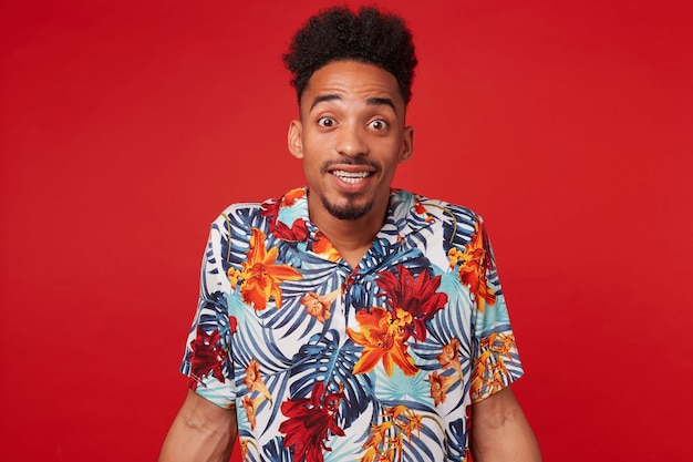 Portret radosnego, młodego afroamerykanina, ubrany w hawajską koszulę, patrzy w kamerę z radosną miną, stoi na czerwonym tle i szeroko się uśmiecha.