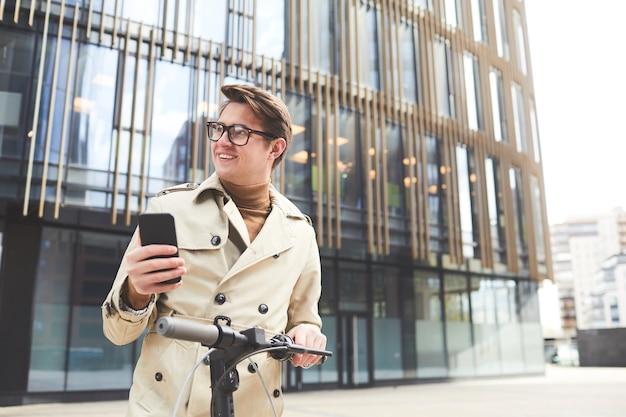 Portret radosnego młodego mężczyzny w płaszczu w pasie, odwracającego wzrok podczas korzystania ze smartfona i jazdy na skuterze elektrycznym z miejskimi budynkami w tle