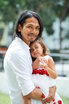Portret radosnego młodzieńca niosącego swoją małą córeczkę w pięknej urodzinowej sukience