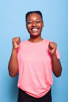 Portret radosnego podekscytowanego afroamerykańskiego nastolatka uśmiechającego się do kamery