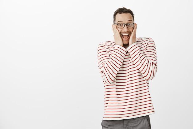 Portret radosnego, wzruszającego przystojnego faceta w okularach, wrzeszczącego z przyjemności i zaskoczenia