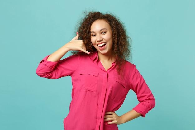 Portret radosnej afrykańskiej dziewczyny w ubranie robi telefon gest jak mówi oddzwoń do mnie na białym tle na tle niebieskiej ściany turkus. ludzie szczere emocje, koncepcja stylu życia. makieta miejsca na kopię.