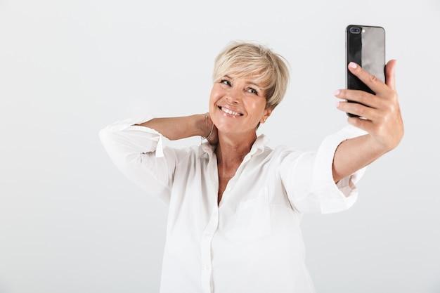 Portret radosnej dorosłej kobiety z krótkimi blond włosami, uśmiechającej się i biorącej selfie portret na telefonie komórkowym na białym tle nad białą ścianą w studio