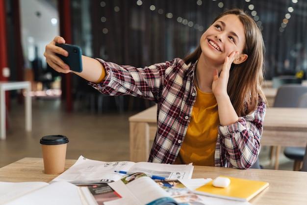Portret radosnej dziewczyny biorącej selfie na telefon komórkowy i uśmiechającej się podczas odrabiania lekcji w bibliotece college'u