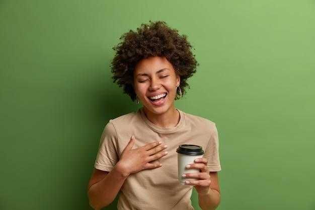 Portret radosnej dziewczyny etnicznej bawi się i głośno śmieje, trzyma jednorazową filiżankę kawy, uśmiecha się szeroko i zamyka oczy, prowadzi wesołą rozmowę, odizolowany na zielonej ścianie. koncepcja stylu życia