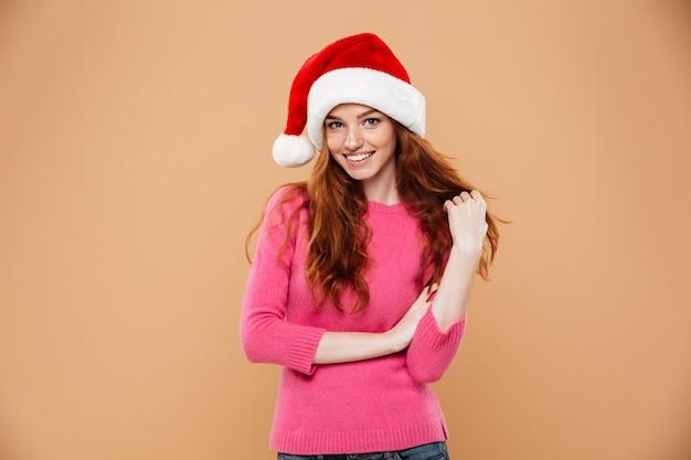 Portret radosnej dziewczyny rude ubrane w świąteczny kapelusz