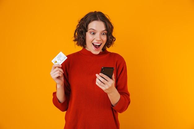 Portret radosnej kobiety 20s ubrana w sweter za pomocą telefonu komórkowego i karty kredytowej, stojąc na białym tle nad żółtym