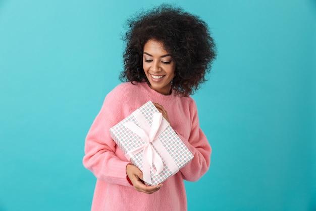 Portret radosnej kobiety 20s z fryzurą afro, trzymając pudełko i uśmiechając się ze szczęścia, na białym tle nad niebieską ścianą